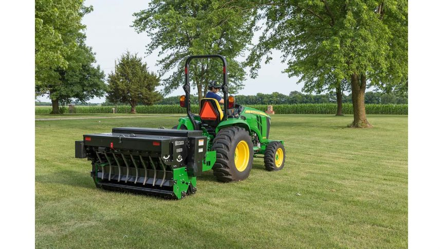 A Frontier GS1160 Overseeder with a John Deere 3039R Compact Utility Tractor over seeding a large lawn.