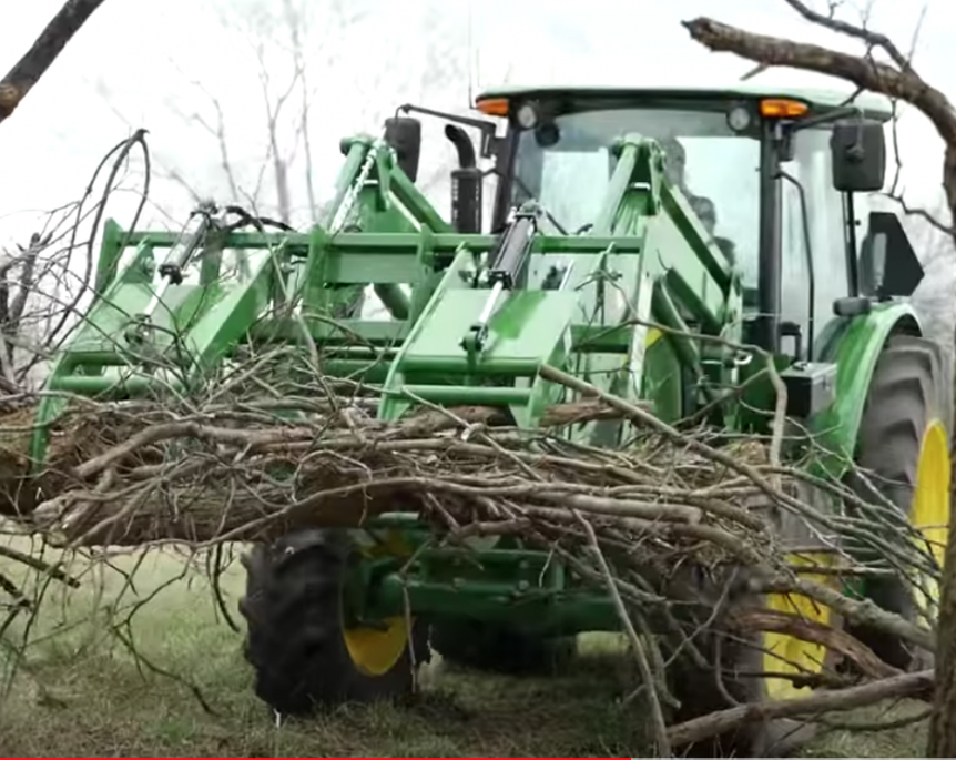 Clearing debris using a Frontier Root Grapple.
